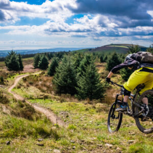Mountain Biking in Wales - rider speeds down steep flowing trail with river Severn in the background. Cwmcarn, Wales.